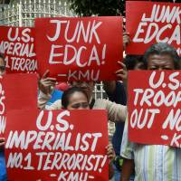 Activists denounce the U.S.-Philippine defense cooperation agreement outside the Supreme Court in Manila on Tuesday. | REUTERS