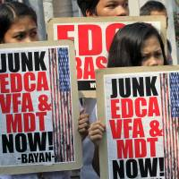 Philippine activists hold placards denouncing the Enhanced Defense Cooperation Agreement with the U.S. during a protest outside the Supreme Court in Manila on Tuesday. | REUTERS