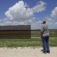 Max Pons, manager of the Nature Conservancy's southernmost preserve, stands near the southern end of the border fence near Brownsville, Texas, on Sept. 17. | AP