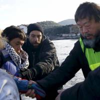 Chinese artist Ai Weiwei (right) helps an Afghan migrant as he arrives with other refugees and migrants on a raft on the Greek island of Lesbos, in this Jan. 25, 2016 file photo. Ai Weiwei is withdrawing an exhibition from Denmark after parliament passed controversial refugee laws on Jan. 26, 2016. | REUTERS