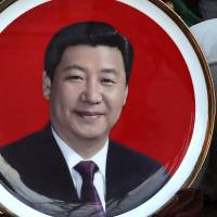 A woman looks at souvenir plates bearing images of Chinese President Xi Jinping and Mao Zedong on display for sale at a shop near Tiananmen Square in Beijing on Sunday. | AP