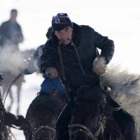 Herders on horses fight for a goat during a buzkashi game at a winter festival in Yining, in the Xinjiang Uighur Autonomous Region of China, on Sunday. The Kazakh festival included games such as horse racing, wrestling and kyz kuu (catch the girl). | REUTERS