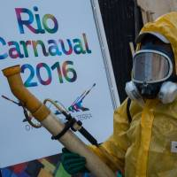 A municipal agent sprays anti-Zika mosquitoes chemical product at the Sambadrome in Rio de Janeiro Monday. Brazil is mobilizing more than 200,000 troops to go 'house to house' in the battle against Zika-carrying mosquitoes, blamed for causing horrific birth defects in a major regional health scare, a report said Monday. | AFP-JIJI