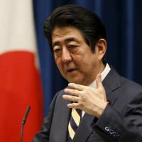 Prime Minister Shinzo Abe addresses reporters on the first official business day of the year during a news conference at his official residence Monday. | REUTERS