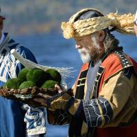 Masao Nishida prays in an Ainu ritual at Hokkaido's Lake Akan in October. Marimo (moss balls) are returned to the lake to thank the gods for a rich harvest. | KYODO