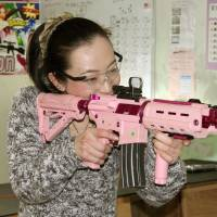 A woman aims for a target with an airsoft gun at Shooting Cafe Rock On in the city of Fukui on Dec. 16. | KYODO