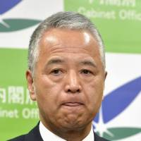 Economy and Fiscal Policy Minister Akira Amari attends a news conference in Tokyo on Friday following allegations that he took money and hospitality from a construction firm. | KYODO
