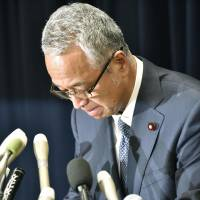Embattled economy minister Akira Amari apologizes at a Cabinet Office news conference Thursday before announcing plans to step down over a money scandal.   KYODO