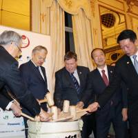 Belgian Foreign Minister Didier Reynders (second from left) and Japan's Senior Vice Foreign Minister Yoji Muto (second from right) break a sake cask Tuesday in Brussels at a ceremony marking 150 years of bilateral relations.   KYODO