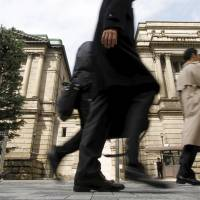 People walk past the Bank of Japan in Tokyo in this March 10, 2010, file photo. The Bank of Japan announced on Friday its decision to introduce negative interest rates. | REUTERS