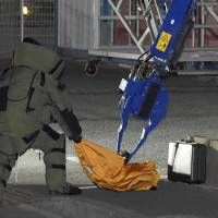 A police officer in protective gear approaches a box suspected of containing an explosive device in a residential area of Ichikawa, Chiba Prefecture, shortly after midnight Saturday. Police later said no explosives were found in it. | KYODO