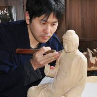 Toshiharu Sakagami, a busshi, or carver of wooden Buddha statues, gets down to work in Kanazawa, Ishikawa Prefecture, on Dec. 14. | KYODO