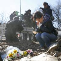 A woman prays Saturday close to the site where a tour bus went off the road east of Karuizawa, Nagano Prefecture, early Friday. | KYODO