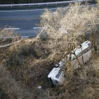 A ski bus is seen on its side off a road in Karuizawa, Nagano Prefecture, Friday morning. | KYODO