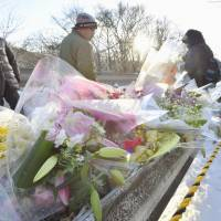 People place flowers Tuesday at a spot along National Route 18 in Karuizawa, Nagano Prefecture, where a ski tour bus carrying several university students crashed last week, killing 15 people. | Kyodo