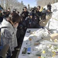 A woman prays Friday at a memorial built where a chartered tour bus crashed leaving 14 dead near the resort town of Karuizawa, Nagano Prefecture, last Friday. One more passenger died a few days later in hospital. | KYODO