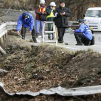 Investigators examine the site of a ski bus crash in Karuizawa, Nagano Prefecture, on Friday. The bus went through a guardrail before rolling. | KYODO