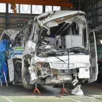 The tour bus that crashed last week near Karuizawa, Nagano Prefecture, is inspected by police in a garage in the city of Ueda on Tuesday. | KYODO