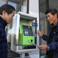 Hiroshi Suzuki (left) checks the procedure to collect coins from a pay phone set up at an emergency meeting point in Tahara, Aichi Prefecture. | CHUNICHI SHIMBUN