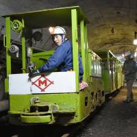 A tram runs through a tunnel in the now-closed Ikeshima coal mine on Dec. 18 in Nagasaki. | KYODO