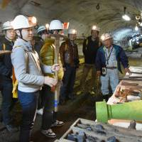 Tourists listen to a former miner (far right) explain the inner workings of the defunct Ikeshima Island coal mine in Nagasaki last month. | KYODO