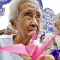 A Filipina survivor of a World War II Japanese military brothel holds a paper crane, a symbol of peace, during a rally in Manila on Wednesday. | KYODO