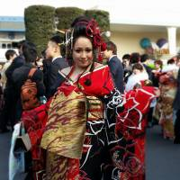 Sayaka Ishida, who was among those attending the Coming-of-Age Day ceremony at Tokyo Disneyland on Monday, said she was glad her kimono in the oiran Edo-Period prostitute style, which cost her ¥300,000, attracted everyone's attention. | TOMOHIRO OSAKI