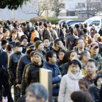 People line up to draw lots for a seat at the first trial session of former Hyogo Prefectural Assembly member Ryutaro Nonomura at the Kobe District Court on Tuesday. | KYODO