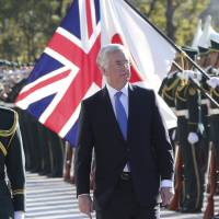 British Defense Secretary Michael Fallon inspects an honor guard at the Defense Ministry before meeting with Defense Minister Gen Nakatani in Tokyo Saturday. | AP