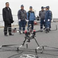 Officers from the Metropolitan Police Department used this black interceptor drone to capture the smaller white drone during an anti-terrorism drill at Tokyo Big Sight in Koto Ward on Sunday. | KYODO