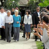 Emperor Akihito and Empress Michiko are greeted by Filipinos who have studied in Japan at San Diego Gardens in Manila on Thursday. | POOL / KYODO