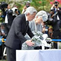 Emperor Akihito and Empress Michiko lay flowers during a visit to the Japanese Memorial Garden in Caliraya, Laguna province, in the Philippines on Friday. | POOL/KYODO