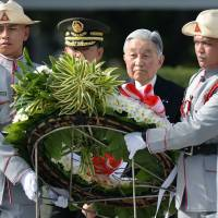 Emperor Akihito follows Philippine soldiers carrying a wreath to the Tomb of the Unknown Soldier during a visit to the national Heroes' Cemetery in Manila on Wednesday. | AFP-JIJI