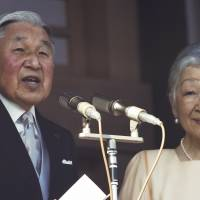 Emperor Akihito delivers a speech to well-wishers from a balcony of the Imperial Palace as Empress Michiko listens during a New Year's public appearance in Tokyo on Saturday. | AP