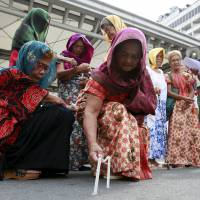 Former Filipino comfort women light candles during a protest in front of the Japanese Embassy in Manila on Friday. | REUTERS