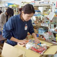 A Food Bank Yamanashi worker prepares a box for families struggling to make ends meet in November. | KYODO