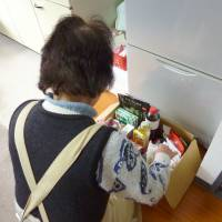 A recipient examines items delivered by Food Bank Yamanashi, a nonprofit organization based in the prefecture, in December. | KYODO