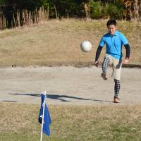 A man kicks a soccer ball from a bunker toward a 50-cm 'cup' on Dec. 9 at Kento's Golf Club in Utsunomiya, Tochigi Prefecture, which has a specialized course for footgolf. | KYODO