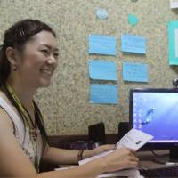 A Japanese woman (left) takes an English lesson from a Filipino teacher at English learning school QQ English, in Cebu, the Philippines, in December 2013. Some people take intensive courses offered by such schools to raise their TOEIC scores. | KYODO