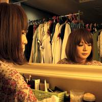 Kuriko, 31, manager of the Onnanoko Club (Girls' Club) cross-dressing bar in Shinjuku, Tokyo, sits in the bar's dressing room on Dec. 27. The bar welcomes anyone wanting to dress up in women's clothing or chat with the cross-dressing staff. | KYODO