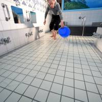 Yasuhiro Tsuchimoto, the fourth owner of the Inariyu sento, pours warm water over the floor when the facility opens in the early afternoon to keep bathers' feet warm. | SATOKO KAWASAKI