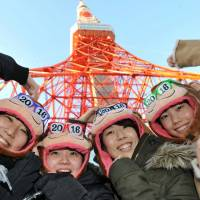 Visitors to Tokyo Tower strike a pose to celebrate the start of the new year Friday morning.   YOSHIAKI MIURA