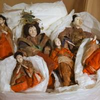 Six hina dolls recovered after being washed away by the March 2011 tsunami in Otsuchi, Iwate Prefecture, are displayed Monday among some 500 dolls and 170 doll ornaments in the Hyakudan Hinamatsuri exhibition in the Meguro Gajoen complex in Tokyo. | SATOKO KAWASAKI
