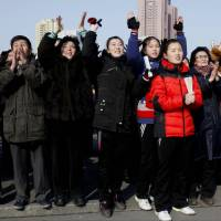 North Koreans watch a news broadcast about the nation's claimed hydrogen bomb test on a video screen outside Pyongyang Railway Station on Wednesday. | AP