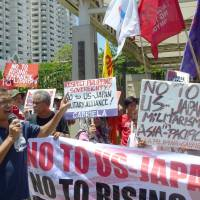 Protesters from a citizens' group demonstrate in front of the Japanese Embassy in Manila against joint Philippine military drills with the U.S. and Japan in June. | KYODO