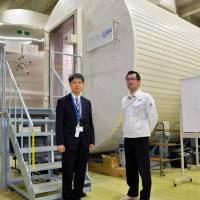 Japan Aerospace Exploration Agency officials show off a test facility in Tsukuba, Ibaraki Prefecture, on Wednesday. | KYODO