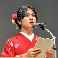 Shunka Hirao, 27, speaks at a Coming-of-Age ceremony for LGBT people in Setagaya Ward, Tokyo, on Saturday. | KYODO