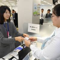 An Itabashi municipal official issues a My Number card Friday at the Itabashi Ward Office in Tokyo. | KYODO