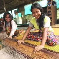 Young girls engage in weaving at the Community Factory operated by the Kamonohashi Project in northwestern Cambodia. | COURTESY OF KAMONOHASHI PROJECT
