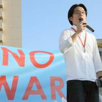 Mitsuhiro Hayashida speaks against the Abe administration's security bills on a street corner in Nagasaki last August. | KYODO
